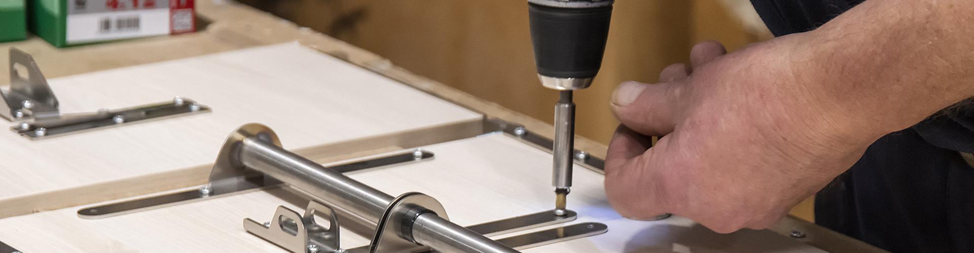 Bilde av hender som monterer et møbel